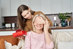 Cute teen child girl, kid daughter having fun covering mum eyes holding present red gift box making Mothers Day surprise greeting happy mom or grandmother on spring holiday at home.
