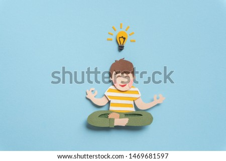 Cute teen concentrating on problem and meditating. Smiling young man with lightbulb having new idea and solution of question. Hand cut illustration from paper