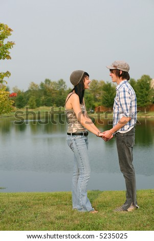 Cute teen couple laughing by a lake - stock photo