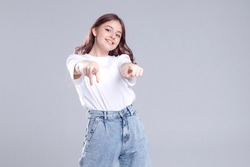 Cute teen girl in a white t-shirt, jeans makes a pointing gesture with her hands. Emotional face. Points directly to you.