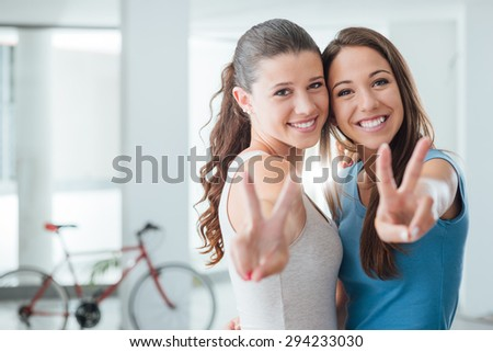 Cute teen girls smiling at camera and making a V sign, adolescence and friendship concept