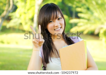 Cute teen with victory sign standing