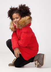 Cute teenage girl in red winter parka sitting against white background