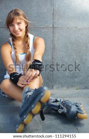 Cute teenage girl in roller skaters looking at camera
