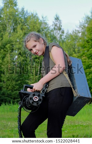 Cute teenage girl playing in lasertag shooting game in open air. Weapon in the hands of people. War simulation.