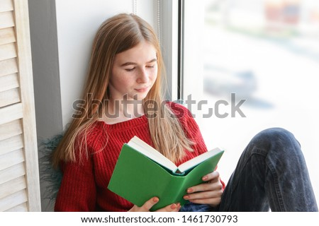 Cute teenage girl reading book on window sill at home #1461730793