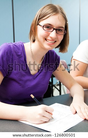 Cute teenage girl taking a standardized test in high school.