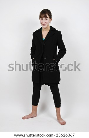 Cute teenage girl without shoes, standing against a white background in a studio.