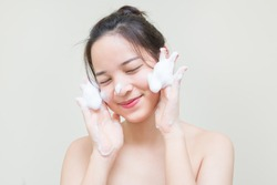 cute teenager Asian girl with baby face skin enjoy herself with bubble cleansing foam