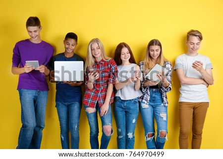 Cute teenagers with modern gadgets on color background