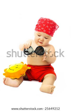 cute ten months old baby wearing summer clothes putting on sunglasses