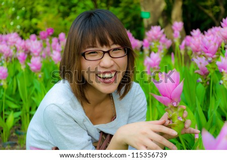 Cute Thai girl are very happy with flowers (Siam Tulip). She is laughing with joy.