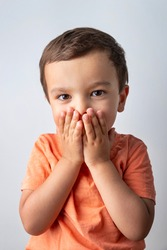 Cute three year old boy portrait, toddler covering his mouth with both hands.