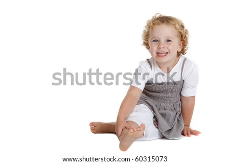 Cute three year old girl sitting on the floor on white background