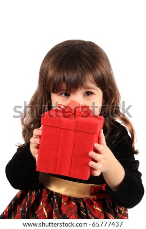 Cute three year old little girl dressed up in a fancy dress hiding behind a red giftbox on a white background