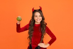 cute to spook. teenage child in imp horns. cheerful kid carry pumpkin. making jack o lantern. carnival costume party. trick or treat. celebrate the holidays. childhood. happy halloween devil girl