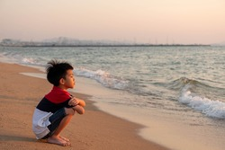 Cute toddler Asian boy sitting alone on the beach at sunset. Child sitting on the beach near sea and looking on the waves, silhouette of the boy on the seaside in sunset.