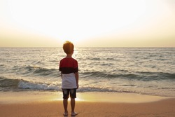 Cute toddler Asian boy standing alone on the beach at sunset. Child standing on the beach near sea and looking on the waves, silhouette of the boy on the seaside in sunset.