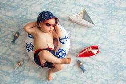 Cute toddler, baby boy sleeping on a tiny inflatable swim ring,  wearing swimsuit shorts and sunglasses, indoor shot