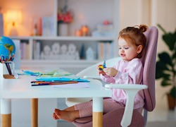 cute toddler baby girl is cutting applique with scissors at home