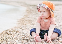 cute toddler baby  sitting on the beach looking at the sea