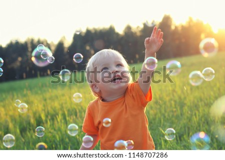 Cute toddler blond boy playing with soap bubbles on summer field. Happy child summertime concept. Authentic lifestyle image.