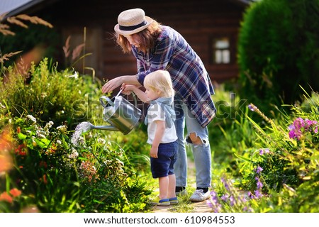 Cute toddler boy and his young mother watering plants in the garden at summer sunny day
