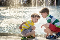 Cute toddler boy and older brother, playing on a jet fountains with water splashing around, summertime concept