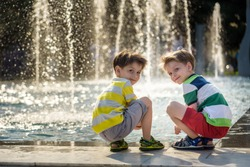 Cute toddler boy and older brothers, playing on a jet fountains with water splashing around, summertime concept