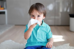 Cute toddler boy blowing nose into tissue paper at home. Mixed race Asian-German baby concept for coronavirus, Covid-19 sickness or allergy.