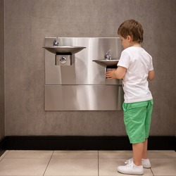 Cute toddler boy drinks water from a drinking fountain in a store. Fountains at different heights for different ages.