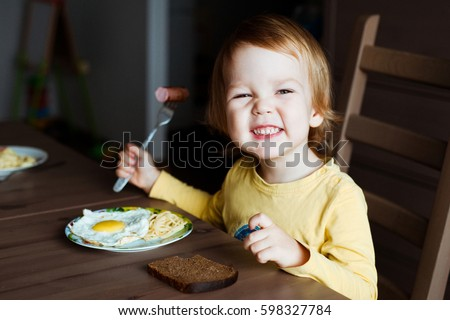 Cute toddler boy eating sausage and eggs for Breakfast.