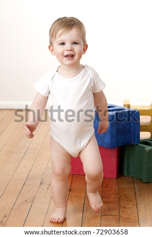 Cute toddler boy learning how to walk.