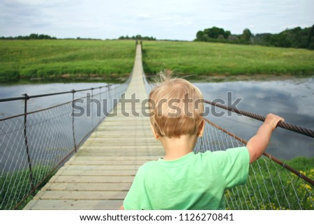 Cute toddler boy overcoming fear, prepering to crossing suspension bridge. Face your fears, look into the future, opening a new way concept.  #1126270841