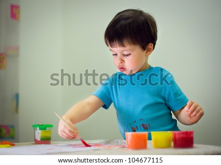 Cute toddler boy painting with brush