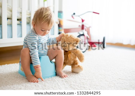 Cute toddler boy, potty training, playing with his teddy bear on potty #1332844295
