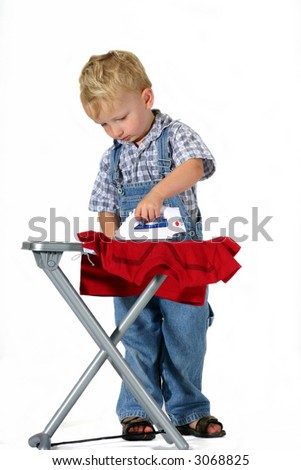 Cute toddler boy pretending to press a t-shirt with a toy iron