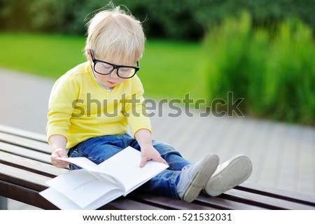 Cute toddler boy reading a book outdoors on warm summer day. Back to school concept