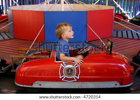 cute toddler boy riding a fire engine on a merry-go-round