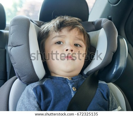 Cute toddler boy sitting in car seat while travel with parent, Safety driving concept for family or child transportation safety, copy space                                 #672325135