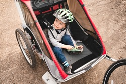 Cute toddler boy sitting in red child stroller. Bicycle trailer has two seats and ready to go.The kid wearing helmet and sport clothes sits in bike trolley pulling by parent's bike..