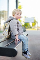 Cute toddler boy sitting on bench on bus stop