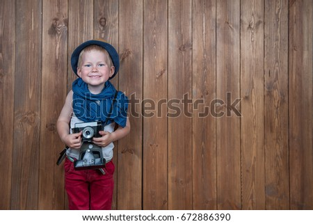 Cute toddler boy with old retro camera on vintage wooden boards abstract background.  Child  with blue eyes in straw hat playing with photo