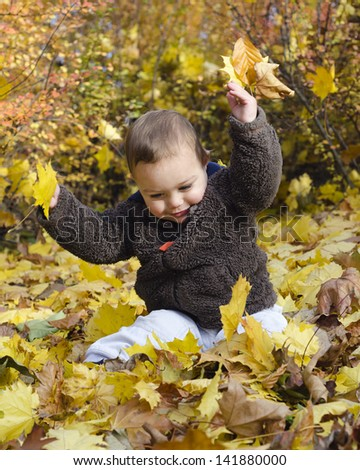 Cute toddler child playing with yellow autumn or fall leaves.