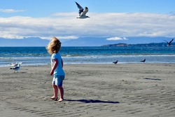 Cute toddler exploring and enjoying the coastal beach for the first time on summer vacation. Family holiday, outdoor lifestyle