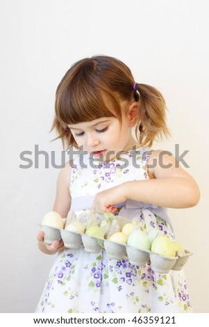 Cute toddler girl counting Easter eggs in the carton box