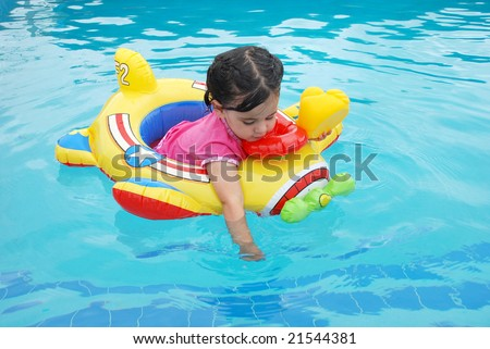 Cute toddler girl floating in a toy plane inflatable in swimming pool playing with a rubber ducky