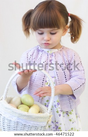 Cute toddler girl holding a basket of Ester eggs
