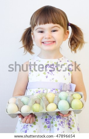 Cute toddler girl holding a carton of Easter eggs