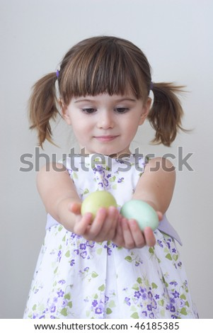 Cute toddler girl holding two colorful Easter eggs in her palms